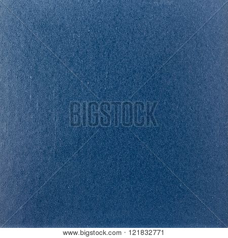Background texture of a shiny metal sheet with a rough stippled textured surface reflecting light. Metal texture
