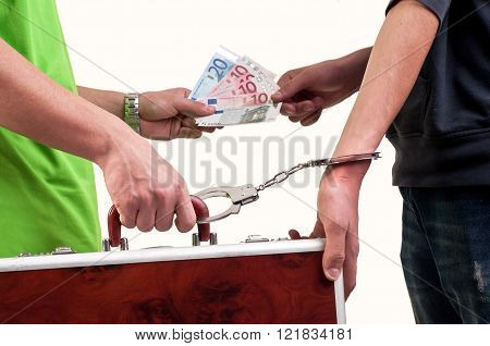 Business transfer deal. exchange between money and suitcase caught by hand with handcuffs