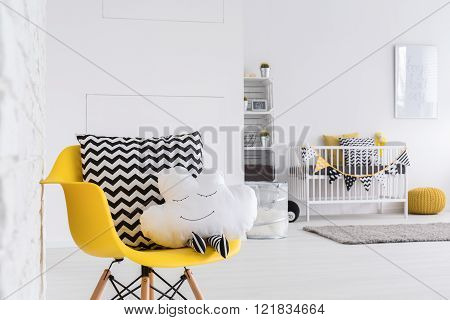Image of a spacious baby room with yellow chair