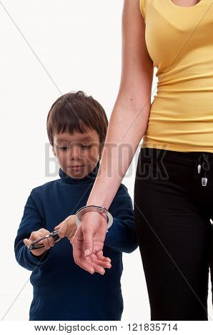Mother and son playing cops and robbers chained with the handcuffs