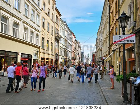 KRAKOW POLAND - JULY 20: People goes by Florianska Main shopping street of Krakow on July 20 2012. Krakow is one the most beautiful and visited cities of Poland.