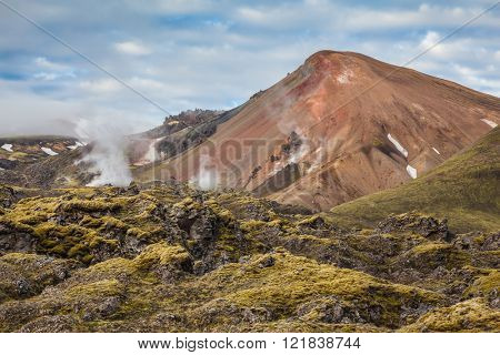 Picturesque rhyolite mountains surround the valley. In the hollows of the mountains from the ground rises 