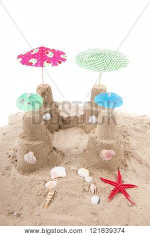 Beach with sandcastle and parasols