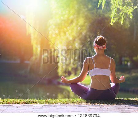 Young woman doing yoga in beautiful morning near lake