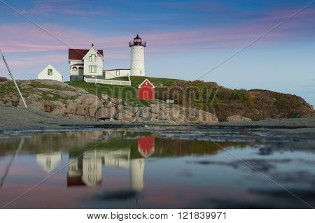 Beautiful colorful Lighthouse along Atlantic Ocean coast in New England marking lighting rocky shore