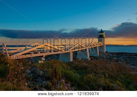Beautiful colorful Lighthouse along Atlantic Ocean coast in New England marking lighting rocky shore at sunset