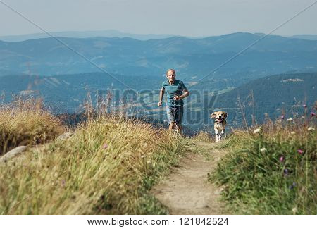 Man runs with his dog on the green meadow in mountain