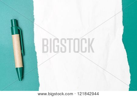Blank note paper crumpled with pen and green background
