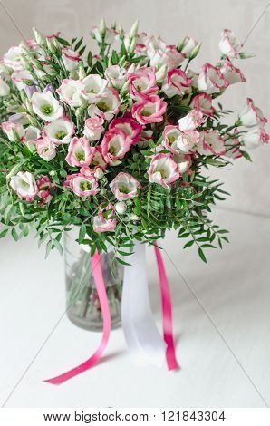 Beautiful Romantic Bouquet Of Pink Eustoma Flowers With Satin Tape In Vase On A White Background