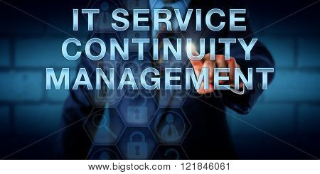 Business continuity manager touching IT SERVICE CONTINUITY MANAGEMENT on a virtual screen. Information technology concept for processes and contingency planning reducing the risk of an IT disaster.