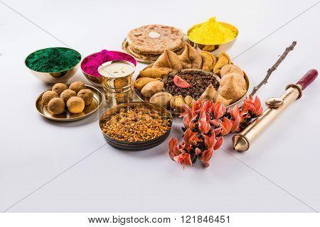 holi festival food with colours, indian festival holi, samosa, kachori, laddu, gujiya, palash flower, thandai, farsan, chana masala, puran poli or roti, indian festival of colours called holi