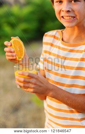 Young kid boy making orange juice, holding glass of juice outdoors