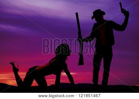A silhouette of a woman on her hands and knees crawling towards a cowboy holding on to a rifle and a pistol.