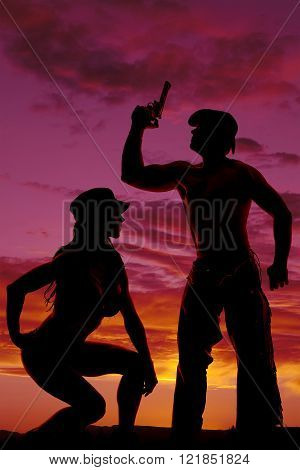 A silhouette of a woman kneeling down while her cowboy uses his pistol to shoot up in the air.