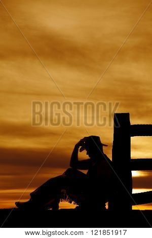A silhouette of a cowboy sitting by a fence, touching his hat.