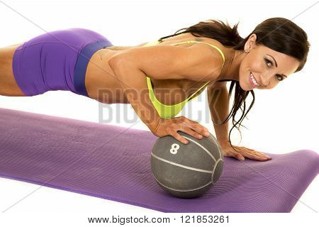 Woman doing a push up on a medicine ball, looking and smiling.