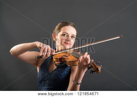 portrait of a beautiful violinist on black background