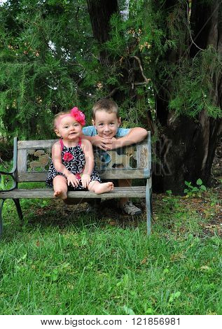 Brother and Sister pose outdoors on park bench. Children are surrounded by green grass and trees.