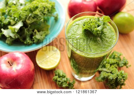 Very healthy smoothie with green kale leafs red apples and lime in a glass