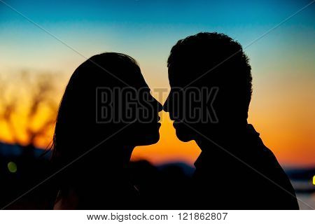 Silhouette of a couple in love. Man and woman kissing on sunset sunset beautiful skyes and romantic atmosphere.