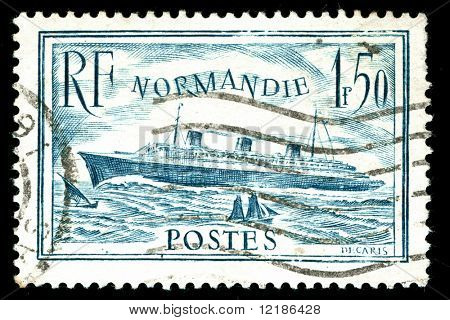 vintage french stamp depicting the launch of the passenger liner SS Normandie in 1932. she is considered to be one of the greatest Ocean liners ever built