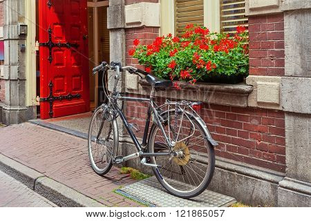Bicycle leaning against brick wall and windowsill with flowers pot in Amsterdam, Netherlands.