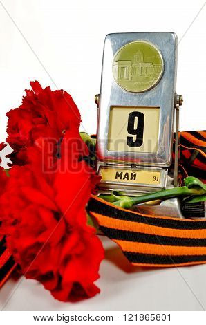 Vintage metal desk calendar with 9th May date and George ribbon with red carnations bouquet - Victory Day concept isolated on white background. Selective focus at the calendar.
