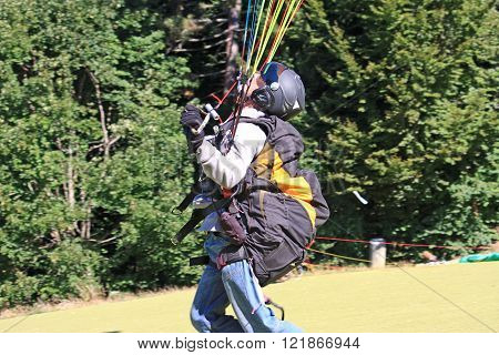 Paraglider about to launch from a hill top