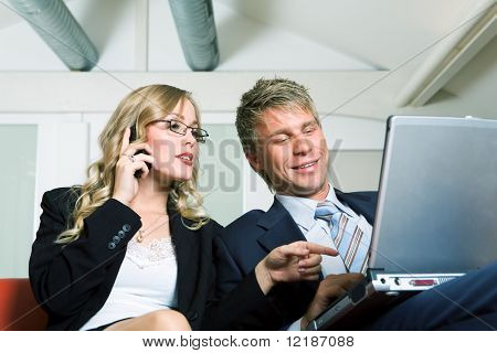 A businesswoman talking to the phone and showing something to her boss