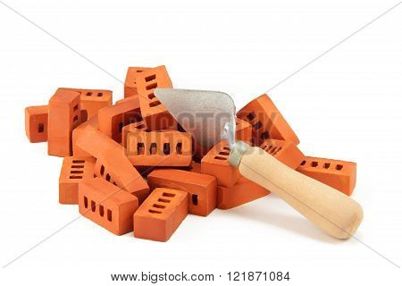 pile of bricks and trowel. toy bricks from clay. construction site. isolated on white background