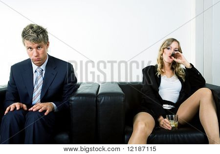 A bossy woman drinking and smoking, a uptight man â?? a metaphor for the battle of the sexes in professional life