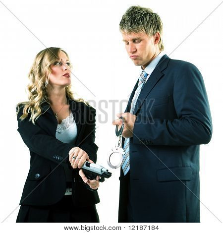 A cop couple, he is holding handcuffs, she is loading a gun