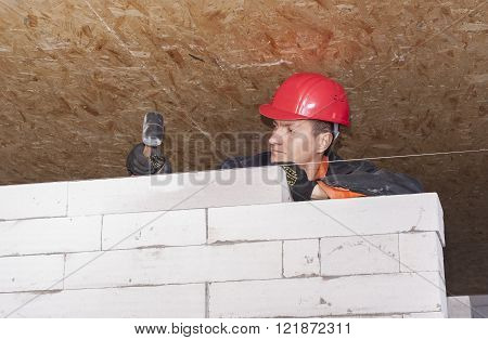 bricklayer puts a wall of aerated concrete blocks