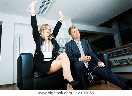 A couple playing a videogame, she is winning and celebrates