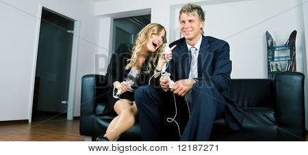 A couple in suits playing videogames, she being more successful that her partner