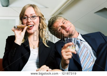 A mini after work party, smoking and drinking business couple (already rather drunk)