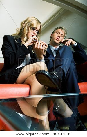 A secretary filing her bosses nails, he is smoking and looking rather arrogant