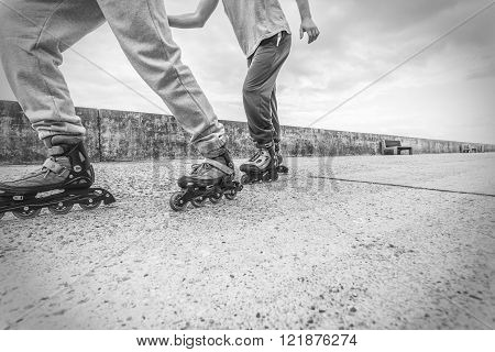Exercising and competition in sport. Healthy lifestyle and wellbeing. Summertime hobby. Young people race together on rollerblades having fun black and white.