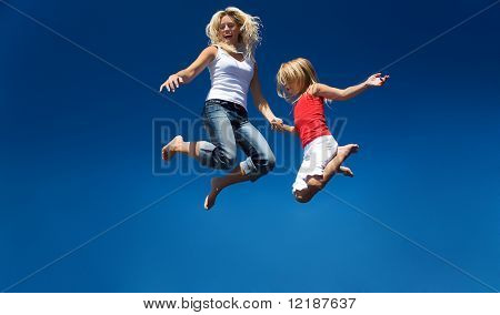 A mother and her daughter jumping high having lots of fun