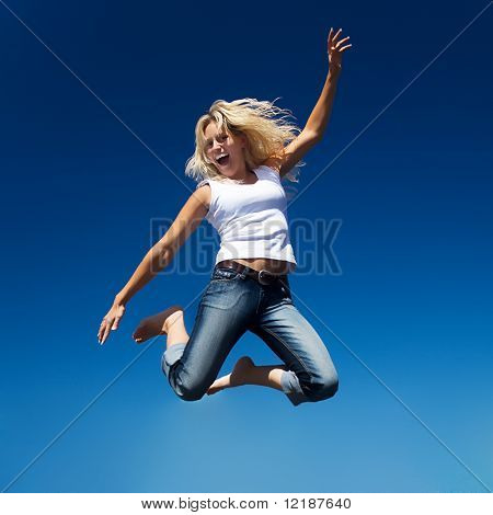 A young and beautiful woman jumping into a perfect blue sky