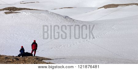 Two Hikers On Halt In Snowy Mountain