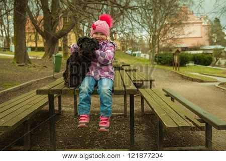 little girl with his black schnauzer dog on a wooden bench