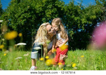Hija besando y abrazando a su madre, ambos de pie en la hierba