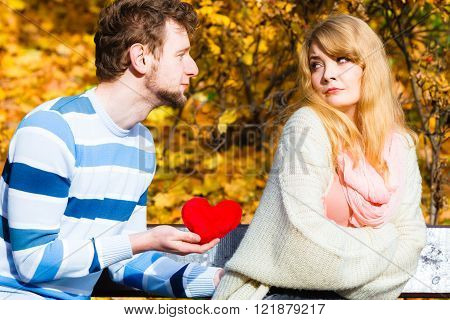 Confessing love and affection with romantic gesture. Rejection and disapproval. Negative reaction. Pair sit on bench in park man hold plush heart showing his emotions girl refuse.