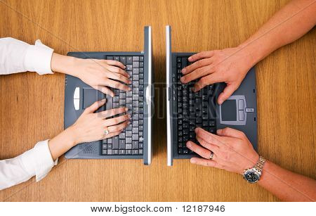 Two people (just hands) working on their laptops opposite of each other (birds view)