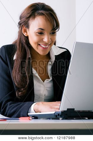 Young woman working on a laptop computer, laughing