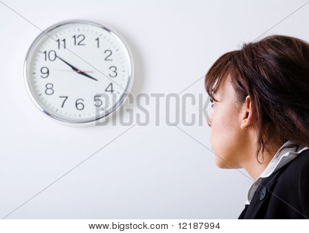 Female office worker looking at a clock on the wall