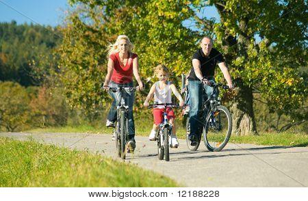 Una familia con los niños que tienen una excursión de fin de semana en sus bicicletas