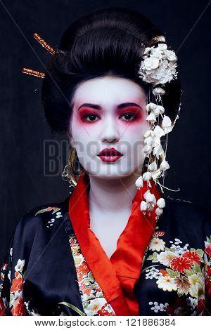 young pretty real geisha in kimono with sakura and decoration