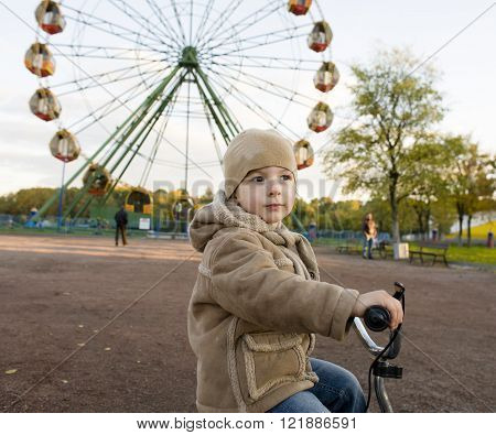 little cute real boy on bicycle emotional smiling close up outside in spring green amusement park